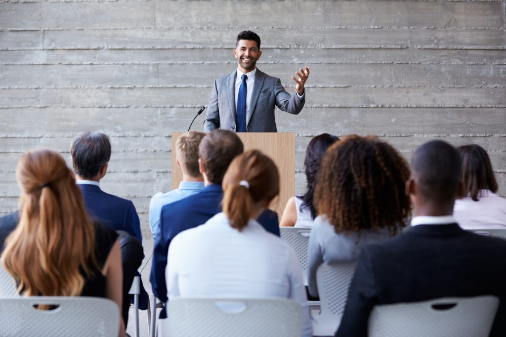 man standing on podium for event tech