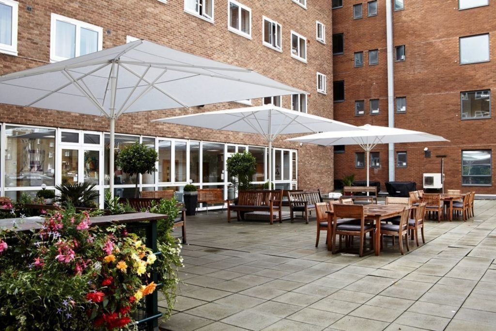 A terrace with wooden tables and open white umbrellas situated outside a red brick building. The terrace has green trees and plotted plants dotted around.