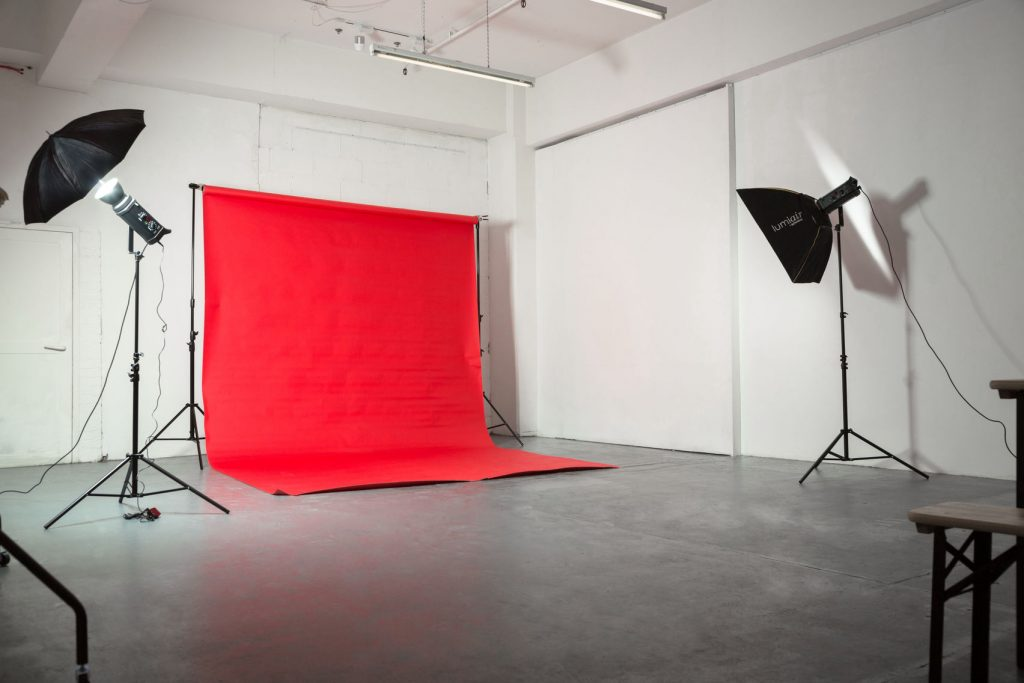 A white walled photography studio with a red backdrop with black photography lights pointing towards it