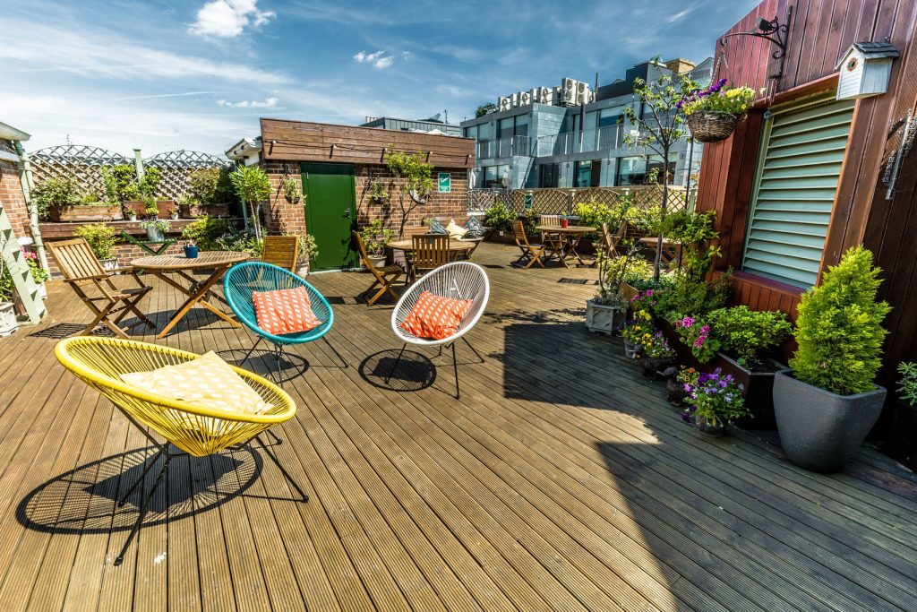 A cosy rooftop terrace with wooden deck floor and bright furnishings with lots of greenery and potted plants