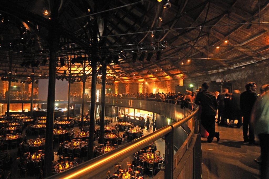 The Roundhouse in London set up as a conference venue. With people standing on the mezzanine level