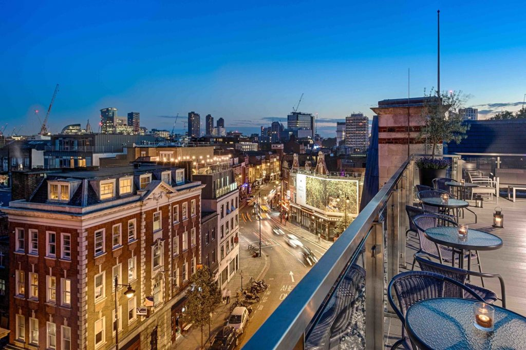 A sky terrace overlooking a busy street in Shoreditch at night time