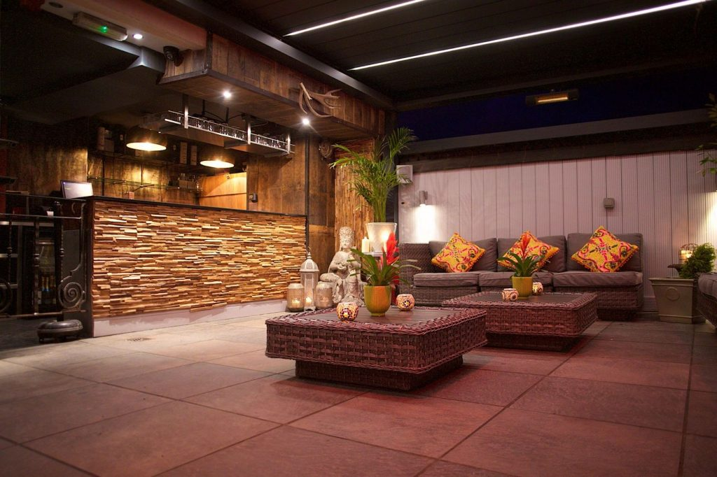 A terrace with two sofas and a separated bar area. It is night time and their are dim orange lights on.