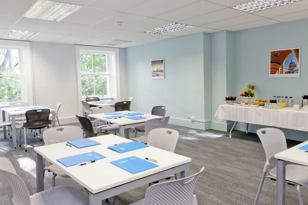 A bright room with 4 square tables each with 4 chairs surrounding them. The room has two big windows letting lots of natural light in and has a blue wall and grey carpet.