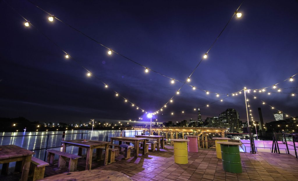 A large open space overlooking tobacco dock in London. Old oil cans are painted in bright colours for bar tables and fairy lights are strung across the width of the terrace