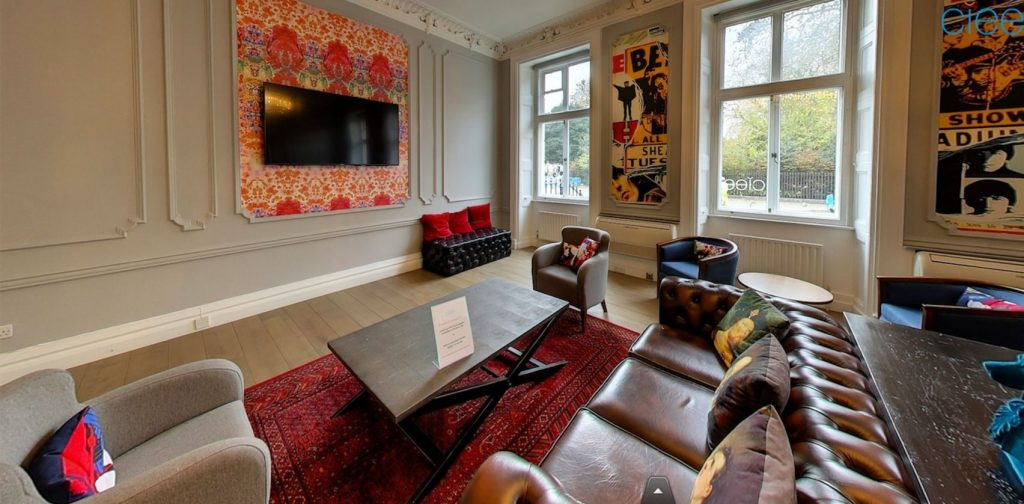 A lounge with a dark leather sofa, chairs and wooden table. Pop art and colourful tapestry's are on the wall