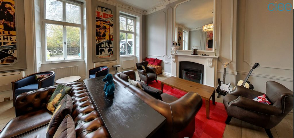 A lounge with dark leather chairs and sofas furnished with colourful soft furnishings, art on the wall, guitars and a red carpet.