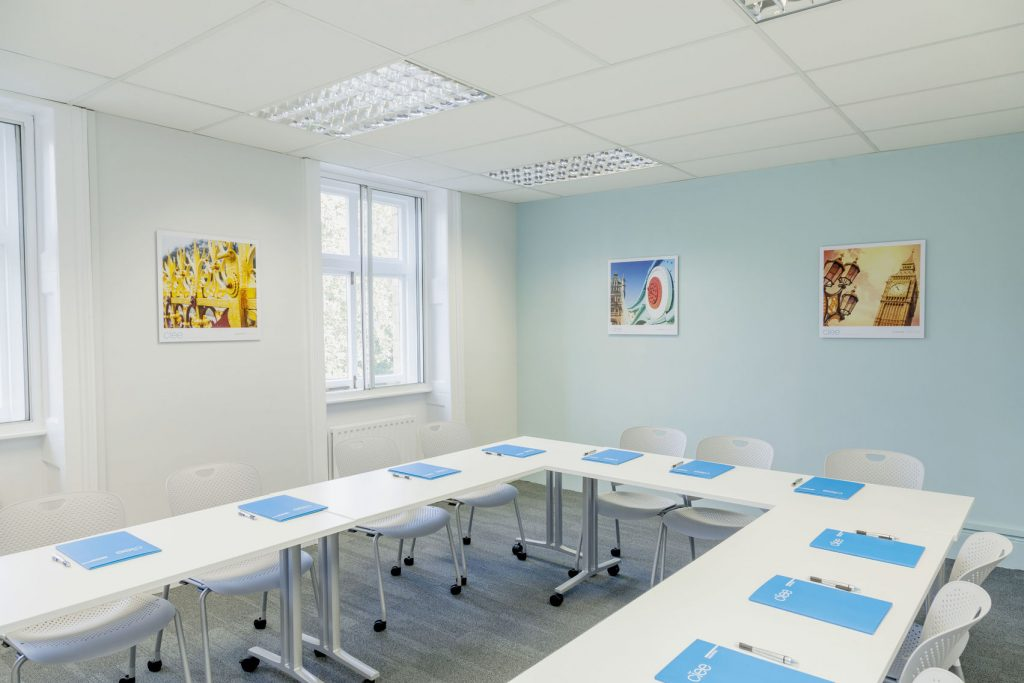 A blue and white room with plenty of natural light and u-shaped table