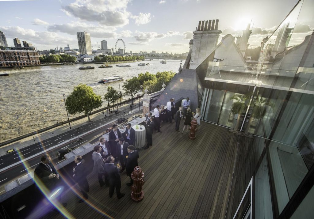 A wooden decked roof terrace next to the river thames. In the background the thames has boats along it and the london eye is visible. Guests are enjoying the sunshine on the terrace, perfect for their summer party.