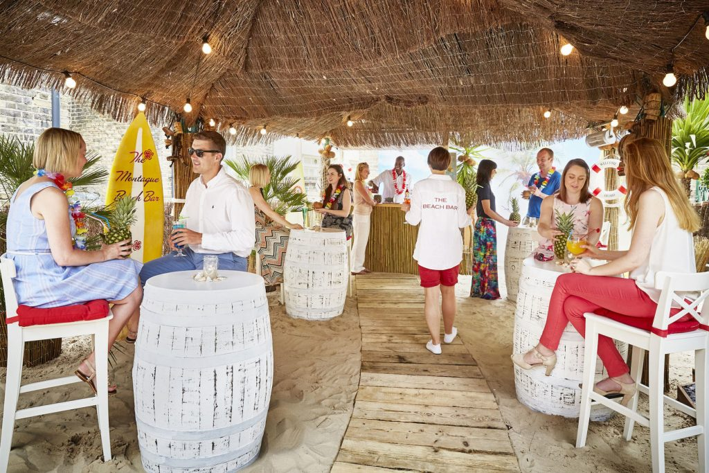 A beach bar with white painted barrel used at bar's. The bar has people in the bar wearing summer clothes with Hawaiian garlands around their neck.