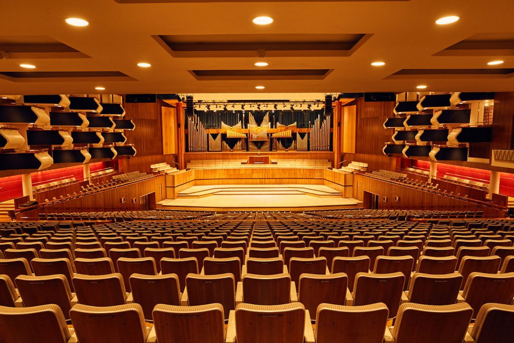 A large conference-style amphitheatre with rows of tiered seats facing the stage