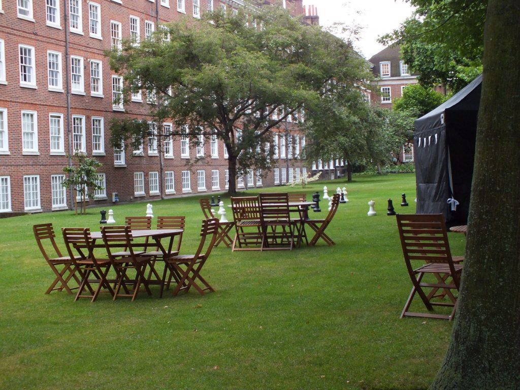 A grassy area with a building in the background, with table and chairs on the grass and a marquee on the right