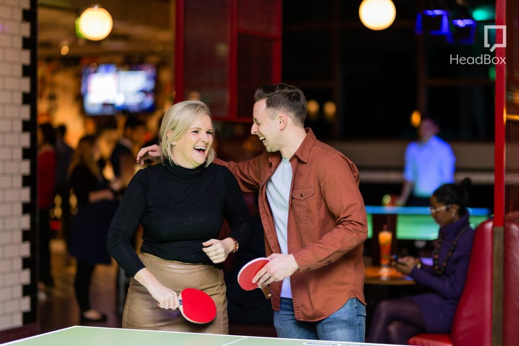 Two people laughing next to a ping pong table with paddles