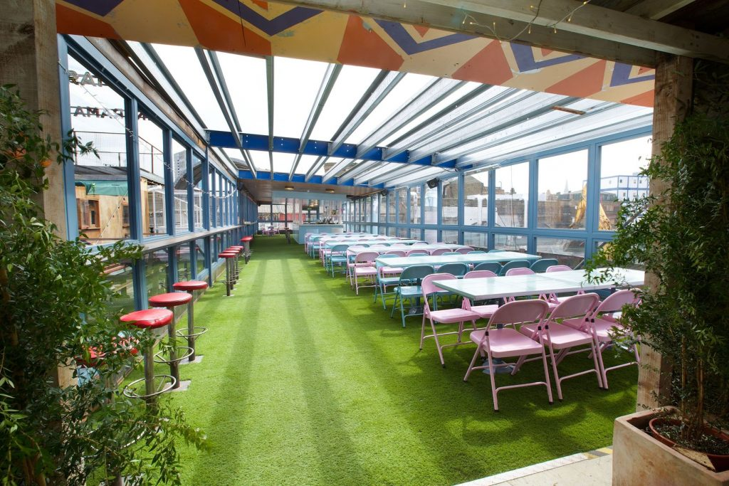 A rooftop bar in dinerama, with astro turf on the floor and bright coloured picnic benches, the perfect unusual summer party venue