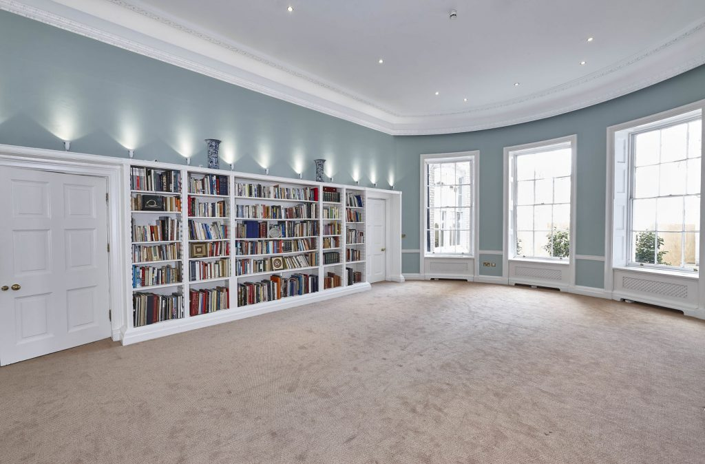 A bright open library with walls on the back wall and big windows on the side wall