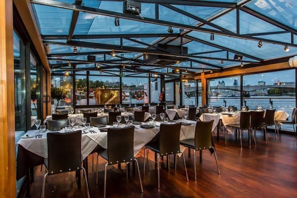 A dining room on a boat with a glass ceiling