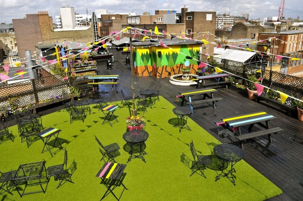 A roof terrace with fake grass, picnic benches and colourful bunting overlooking the city
