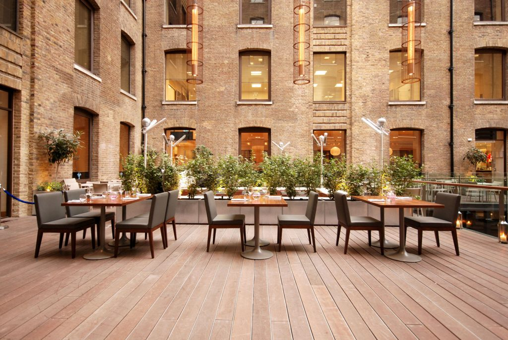A large patio, terrace area with wooden decking and table and chairs situated in a courtyard
