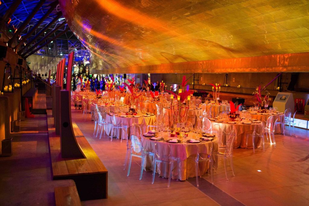 A cabaret style seating under the hull of a boat, otherwise known as the famous cutty sark. The Space is lit with red and orange bright lighting.