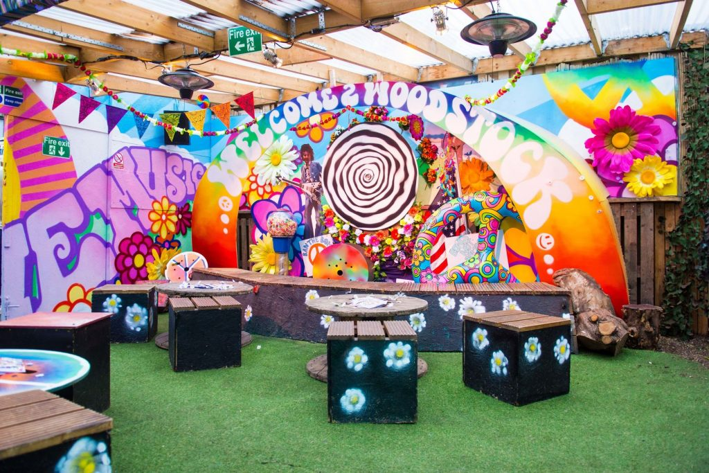 A brightly coloured bar with brightly coloured paintings on the back wall and fake grass on the floor. The perfect unusual summer party venue for your next summer party