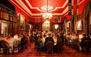 banquet hall with red ceilings and wooden floors with guests sat at round tables