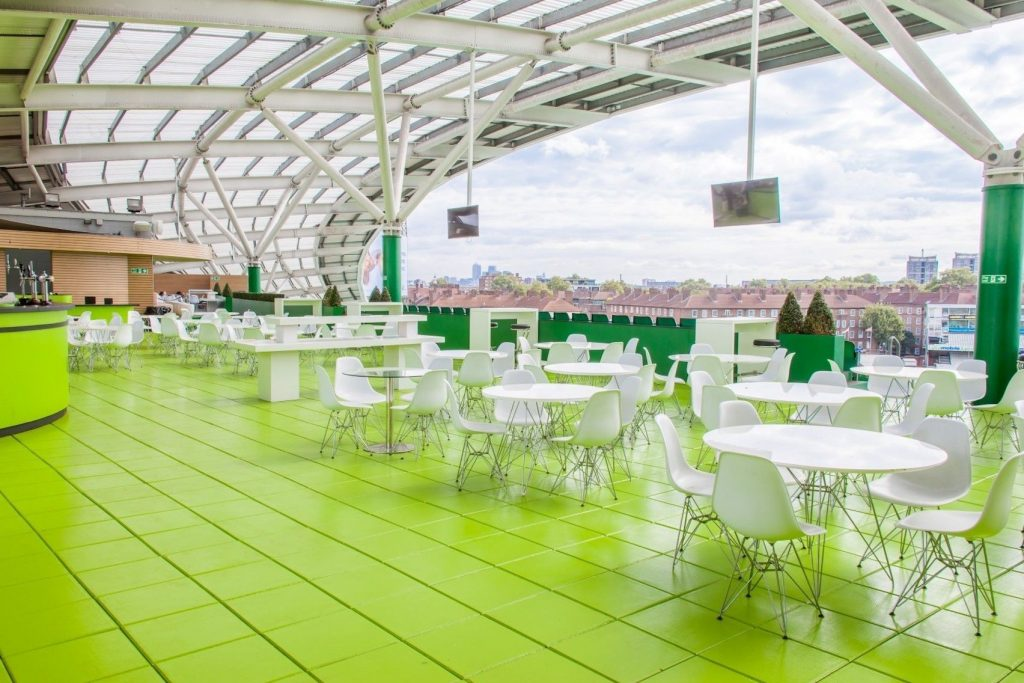 A large roof terrace with green tiled floor and white furtinture overlooking rows of houses