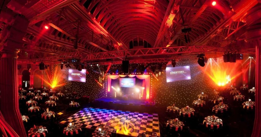 A large party room with a dance floor, circular table and disco lights