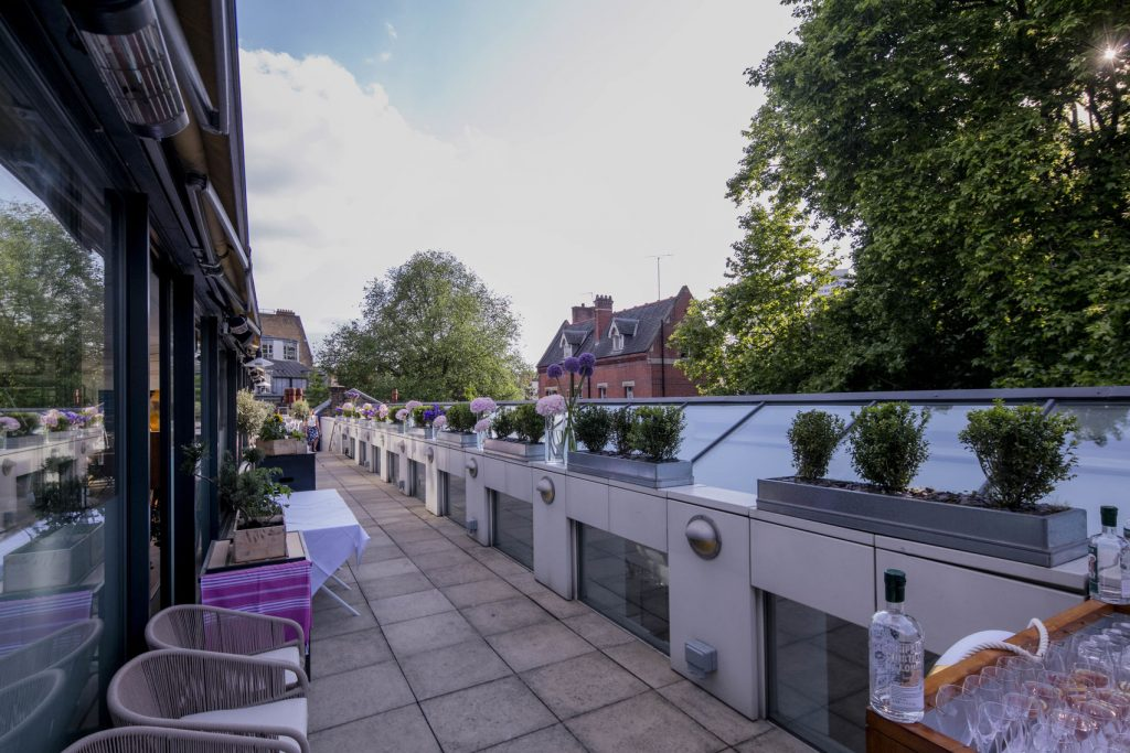narrow roof terrace lined with flowers