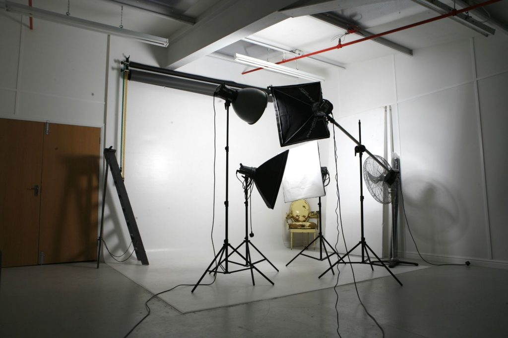 A white photo studio with photography equipment and big studio lights placed around.