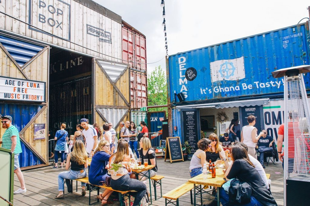 Pop Brixton is a street food and creative space made up of old sea containers and has food benches throughout with people sitting on them enjoying the sun
