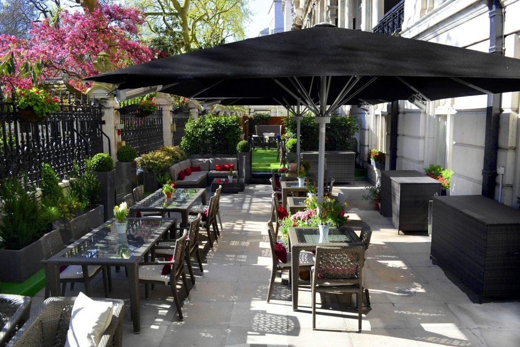 A small roof terrace with table and chairs and umbrellas