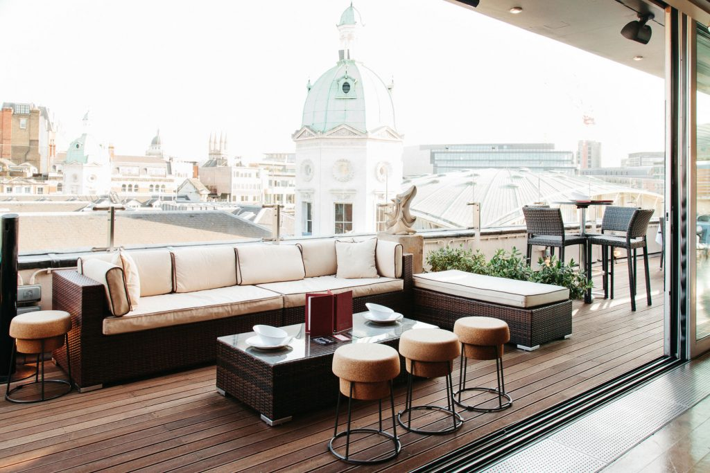 A terrace overlooking London. With with white sofas, chairs and stools. The perfect summer party location