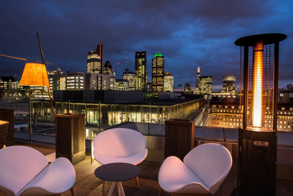 A roof terrace with pink chairs over looking the London skyline