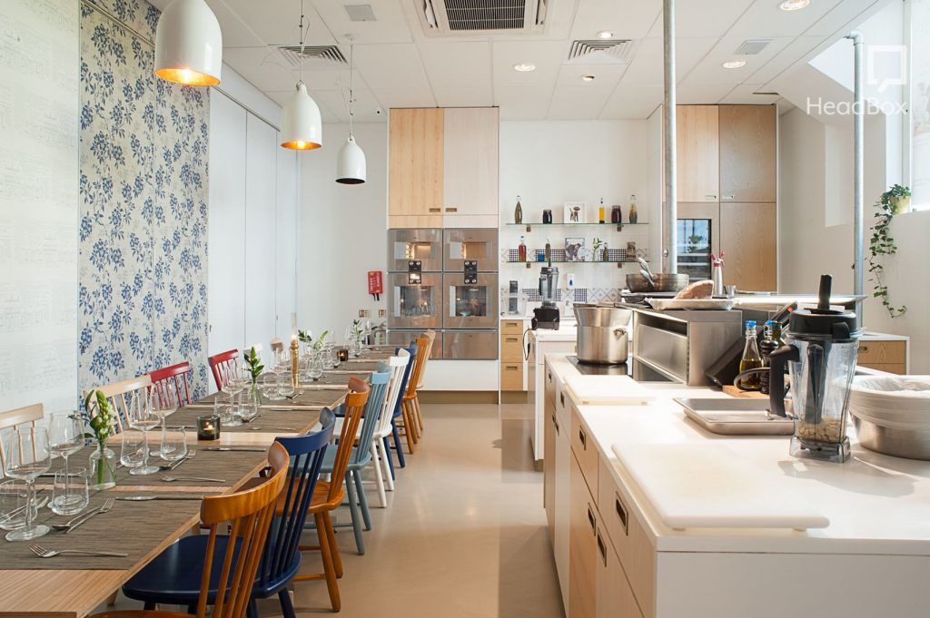 A kitchen school creative space. WIth a large cooking space then tables and chairs set for dinner.