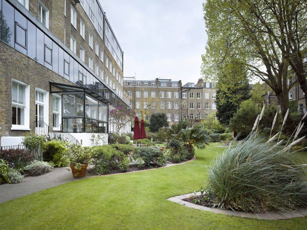 A large grass patch in the middle square of buildings. A grass and garden patch runs through in a curved space