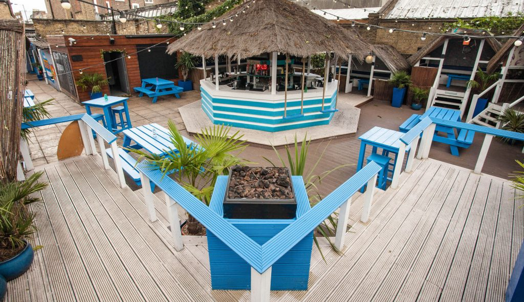 A large outdoor venue in London. The space has wooden floor and large thatched-roof huts.