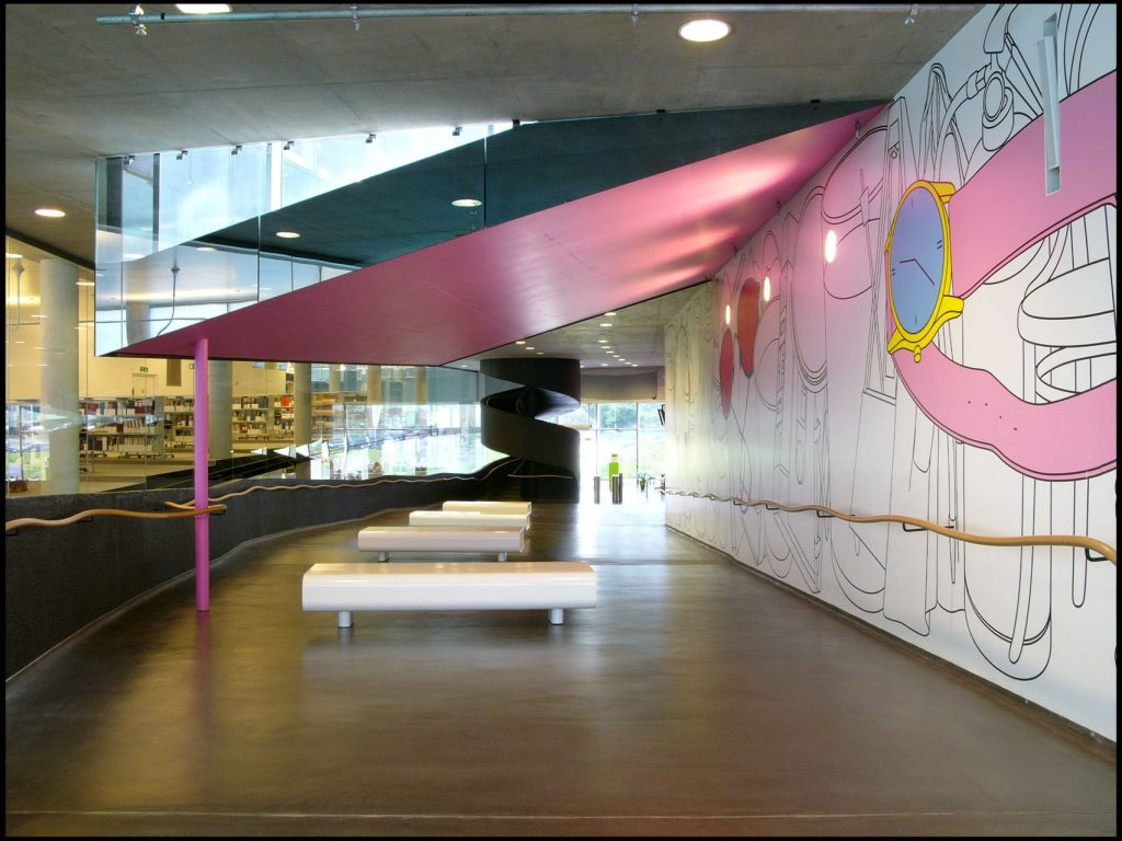 The foyer of the Laban building is painted with a colourful mural on one wall and has sofas in the background.