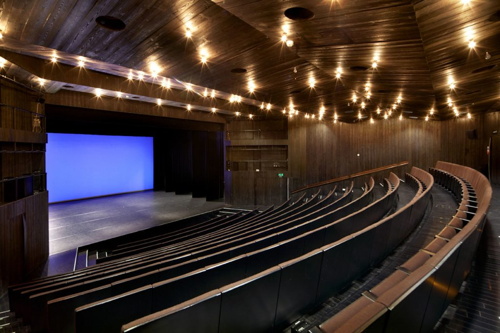 An indoor theatre with dark wooden seating and stage and with spotlights in the ceiling. A great option for venue hire in London