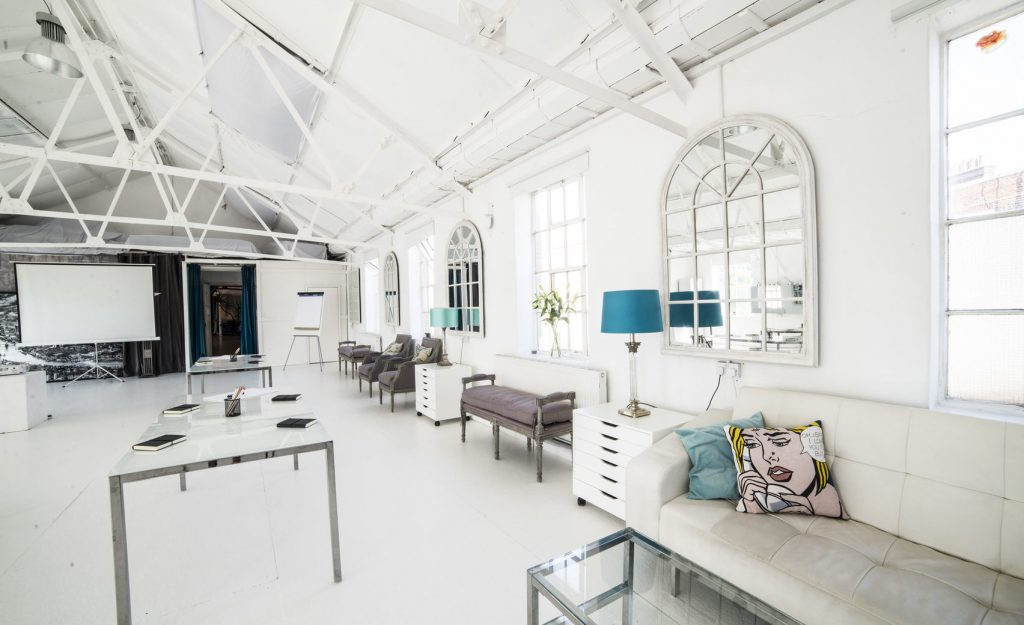 A white loft with white and blue furnishings. A light, bright creative space in London.