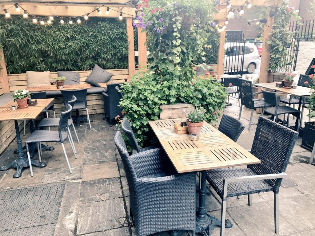 An outdoor terrace in London. With chairs tables and a pergola.