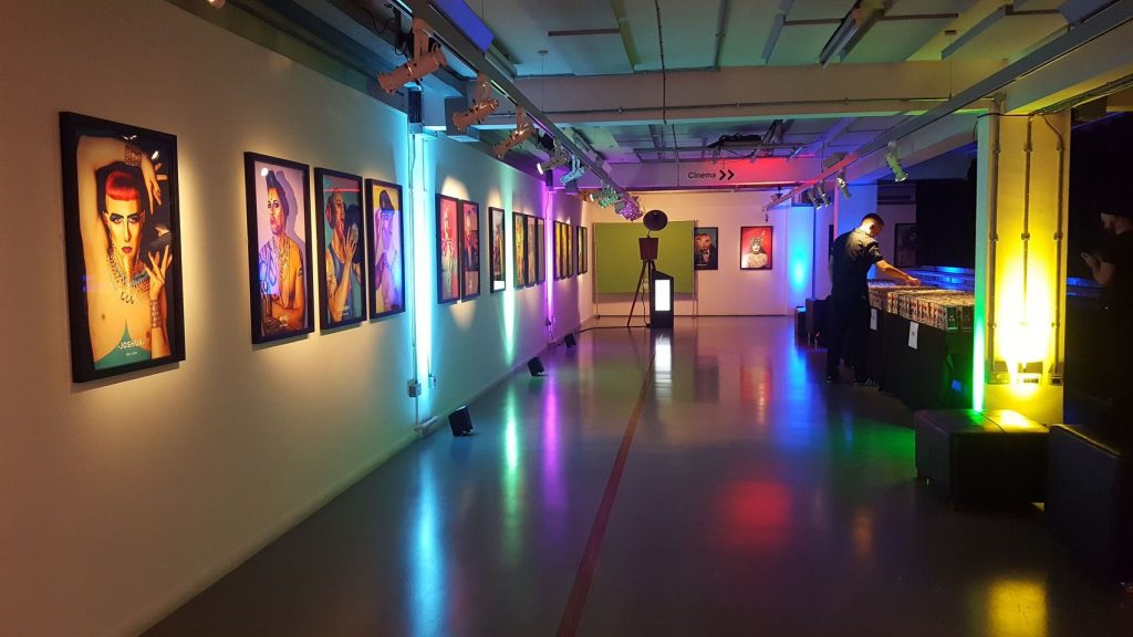 A gallery space lit up with coloured lights.