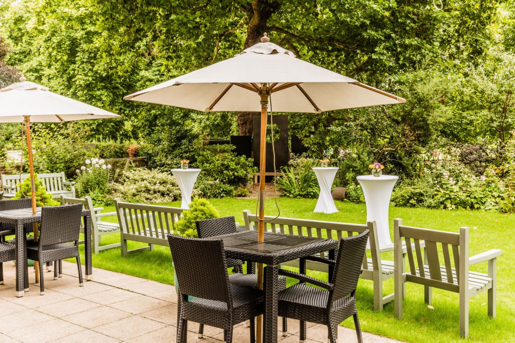 An outdoor venue in London with chairs and tables on a large grass patch and separate paved area