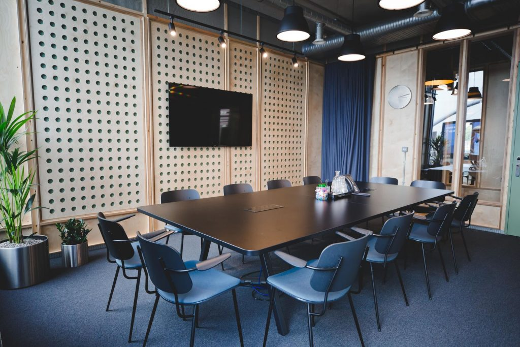 A modern meeting room in London with blue velvet chairs and dark wood table