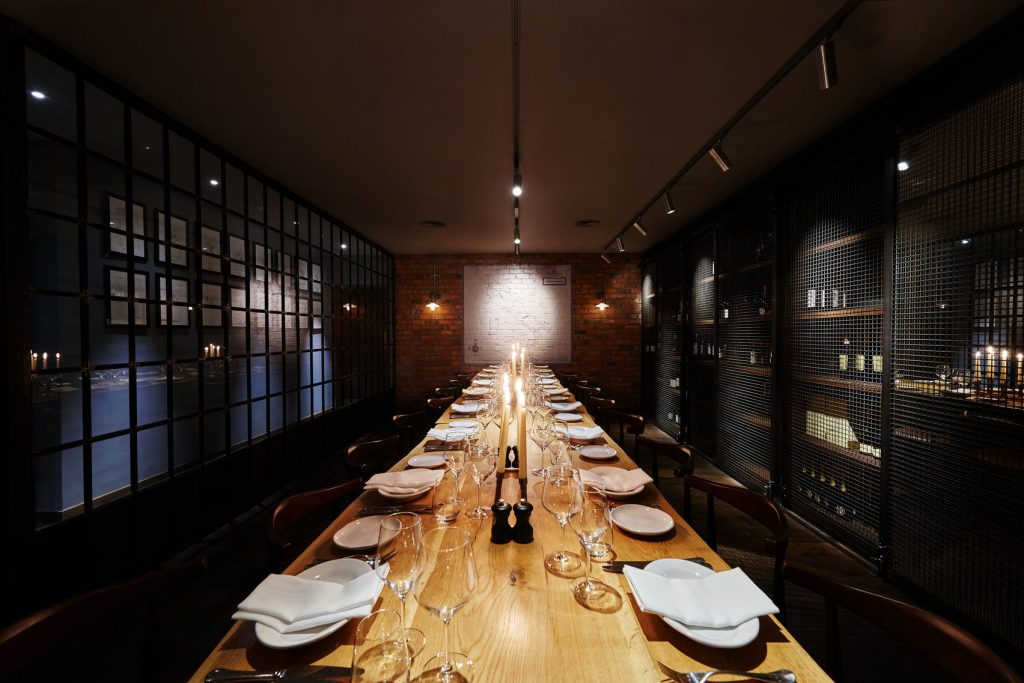A dimly lit private dining room, with metal cage like walls and a light oak table.