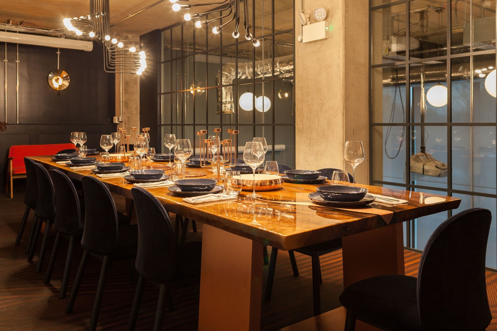 A private dining room with a glass wall and low hanging lights