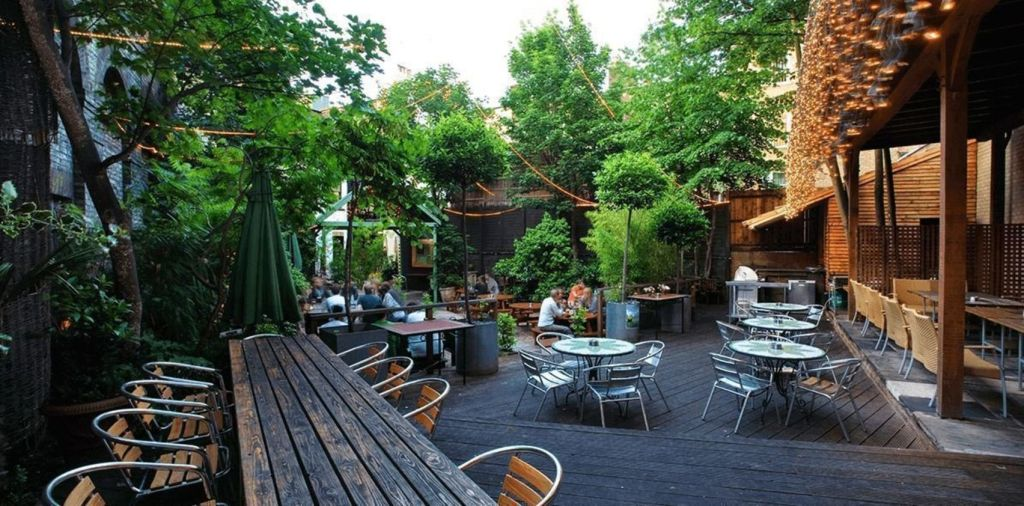 A terrace area with lots of trees and tables and chairs. The ideal outdoor venue in London