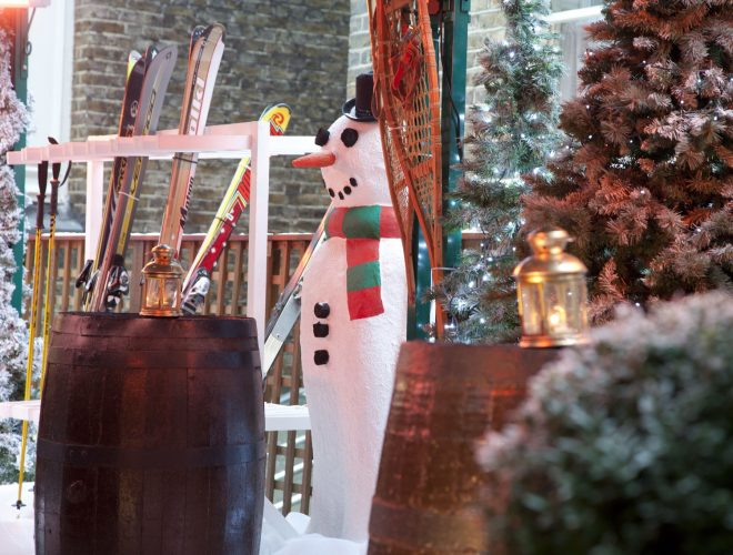 A winter wonderland scene with quirky interior including a snowman, skis and Christmas trees.