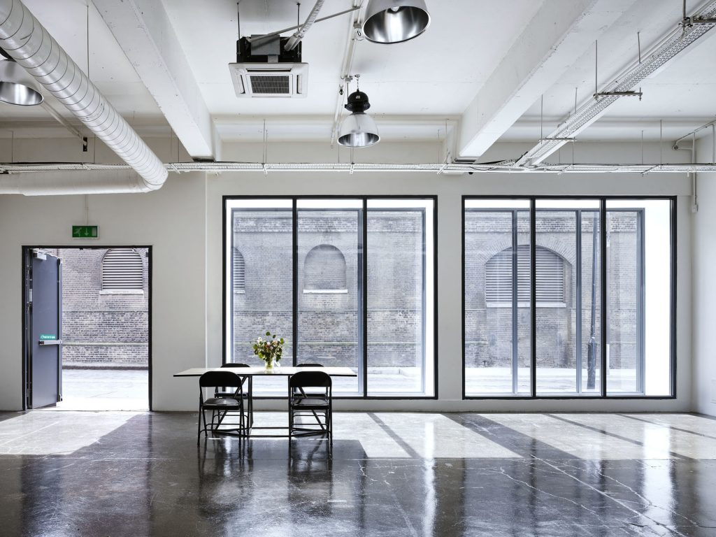 A large white, open studio with floor to ceiling windows