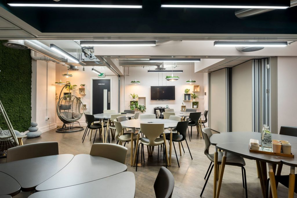 A large conference room or meeting room in London. With modern furniture, green plants and pink walls. It's a great Space for