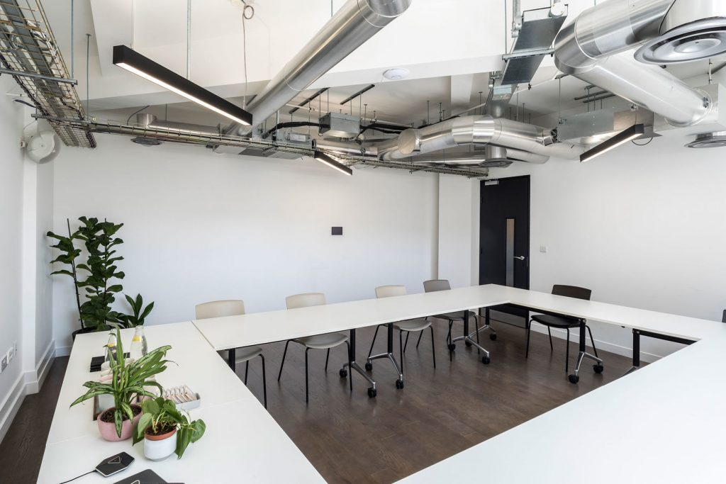 A large meeting room in the city. With white walls and configured in boardroom meeting style. This is a great option for venue hire London.
